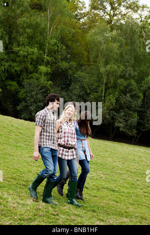 Young adult friends walking down hill - Stock Photo