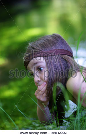 Little boy playing alone next to a small river - Stock Photo