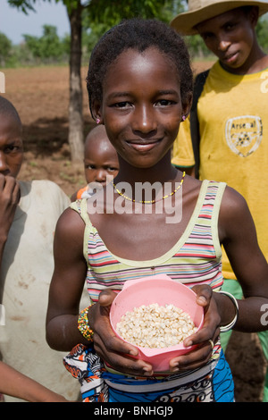 A young girl helping with the sowing of the maize crop in a Fulani compound in a village in Damango district, Ghana. - Stock Photo