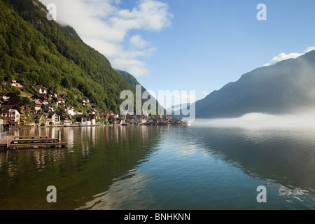 Tranquil view across calm waters of lake Hallstattersee to World Cultural Heritage lakeside town in Austrian Alps. - Stock Photo