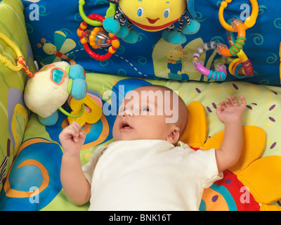 Six week old cute baby boy lying in a colorful play mat with toys - Stockfoto