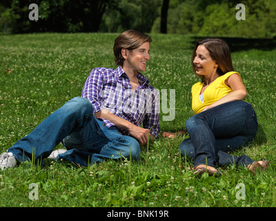 Young happy couple in their early thirties lying on grass in a park - Stock Photo