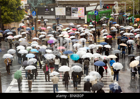 People on the Shibuya zebra crossing in the rain, Tokyo, Japan - Stock Photo