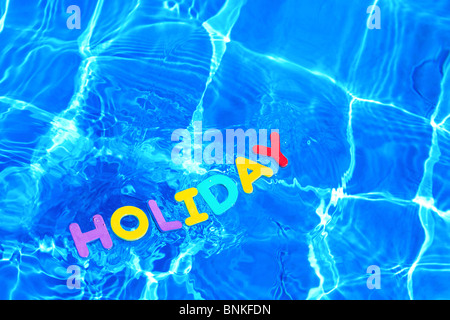 The word HOLIDAY made from foam letters floating on the water surface of a swimming pool - Stock Photo