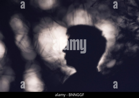 The soft shadow of a young man's head in profile, cast against a wall in dappled light with the shadows of shrubs - Stock Photo
