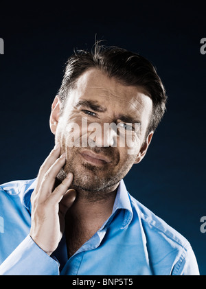 caucasian man unshaven toothache portrait isolated studio on black background - Stock Photo