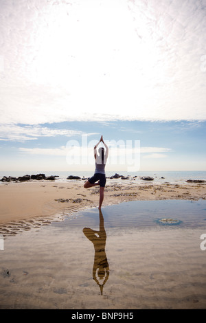 Back view of a woman practicing yoga on a beach - Stock Photo