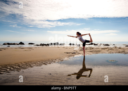 Woman practicing yoga on a beach - Stock Photo