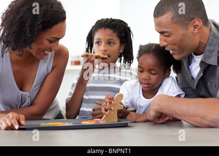 Happy family eating homemade biscuits - Stock Photo