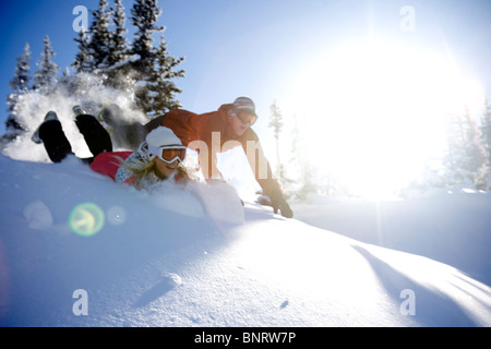 A man and woman play in the snow in the mountains. - Stockfoto