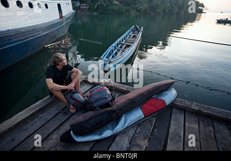 Man sitting on a dock beside travel bags and surfboards, wearing shorts in the tropics. - Stockfoto