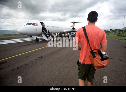 Tall man with shoulder bag walks to airplane. - Stock Photo