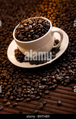 Cup filled with delicious roasted coffee beans - Stock Photo