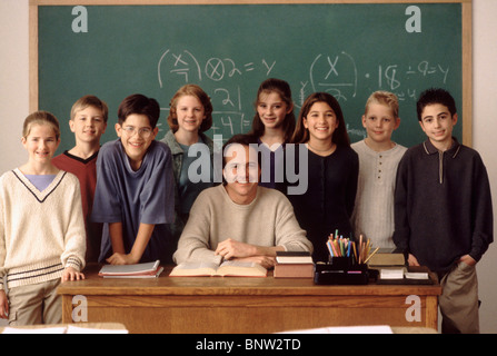 Elementary school students standing behind teacher - Stock Photo