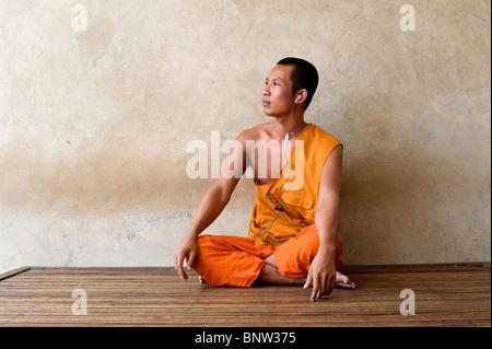 A Buddhist monk with headphones, Phnom Penh, Cambodia - Stock Photo