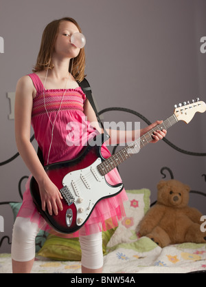 Young girls playing guitar on her bed - Stock Photo