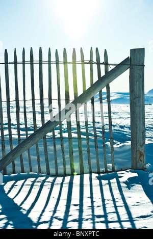 Wooden fence in snowy landscape - Stock Photo