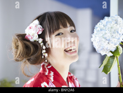 Young woman holding hydrangea - Stock Photo