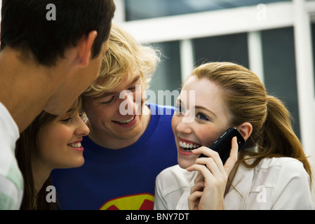 Young friends gathered around teen girl using cell phone - Stock Photo