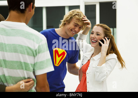Young friends hanging out, one talking on cell phone - Stock Photo
