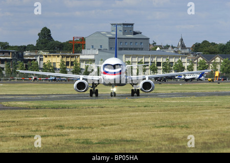 Sukhoi Superjet 100 taxiing out onto the runway at the Farnborough Airshow - Stock Photo