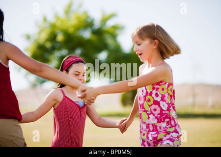 Girls holding hands dancing in a circle - Stock Photo