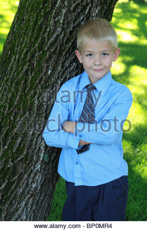 A sharply dressed 5 year old boy leaning against a tree. - Stock Photo