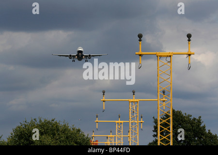 An aircraft on final approach for Heathrow Airport, London, with two more planes in the approach queue visible in - Stock Photo