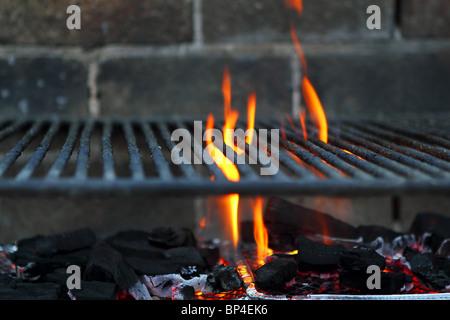 Bar b cue barbecue fire BBQ coal fire iron grill brick wall - Stock Photo