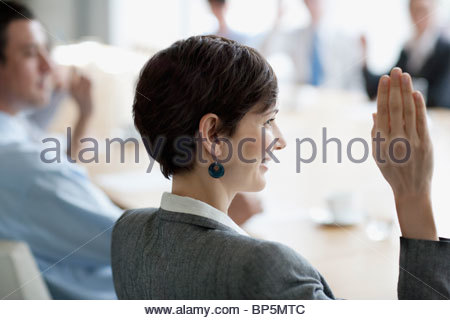 Business people raising hands in meeting in conference room - Stock Photo