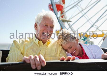 Laughing senior couple on amusement park ride - Stock Photo
