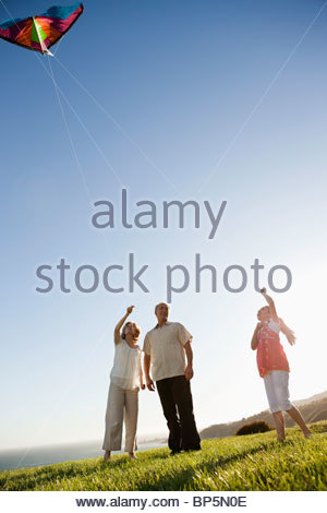 Grandparents and granddaughter flying kite on grass overlooking ocean - Stock Photo