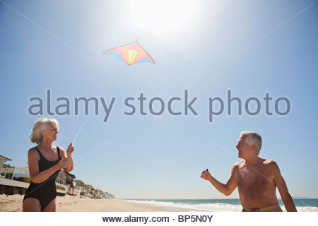 Senior couple flying kite on beach - Stock Photo