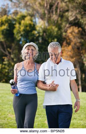 Smiling senior couple walking and holding hands - Stock Photo