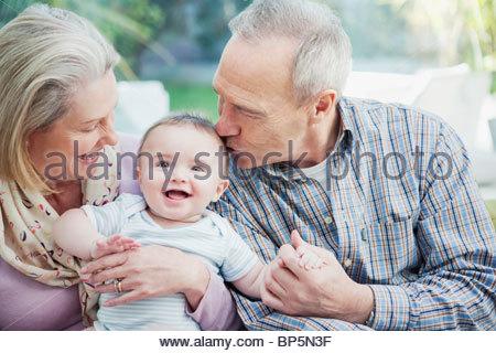 Grandparents holding baby grandson - Stock Photo