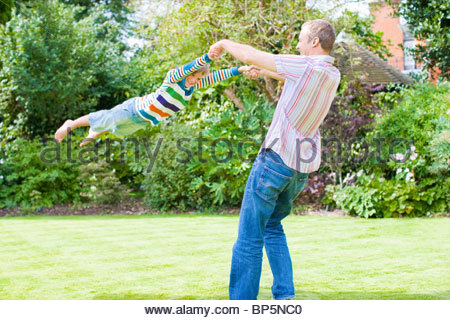 Father swinging son in backyard - Stock Photo