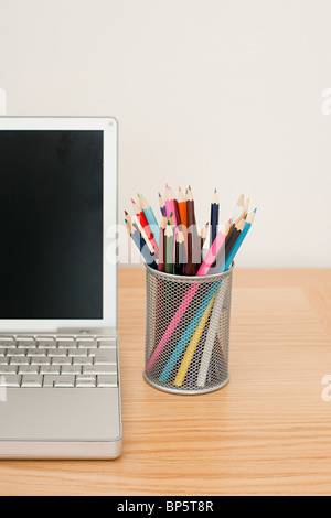 Colored pencils and laptop - Stock Photo