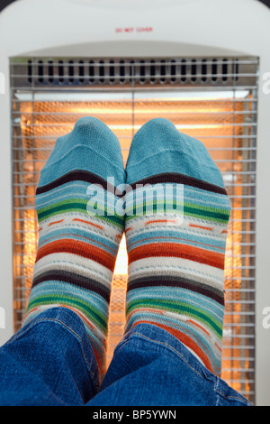 Person wearing colourful matching pair striped woolly socks warming feet in front of a low energy electric Halogen - Stock Photo