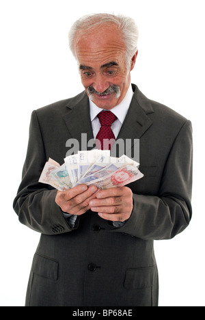 Senior looking very happy holding an assortment of British banknotes - Stock Photo
