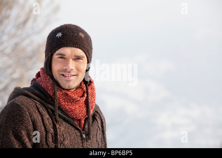 Young man in winter clothes smiling at camera - Stock Photo