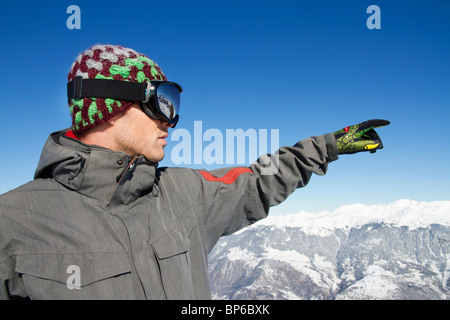Portrait of young man in ski wear pointing - Stock Photo
