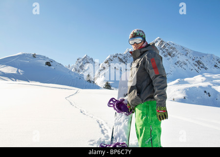 Young man with snowboard in snow - Stock Photo