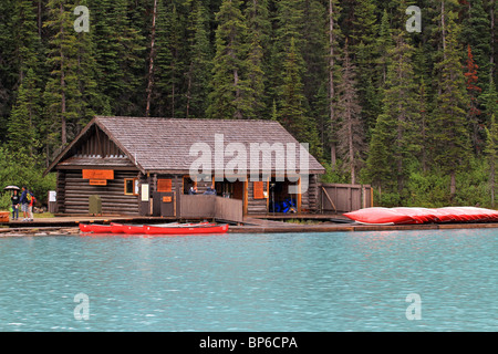 Canoes by boat house on mountain forest lake in Banff National Park, Canada. Lake Louise during rain. - Stockfoto