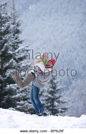 Man lifting girlfriend in snow on remote snowy hillside - Stockfoto