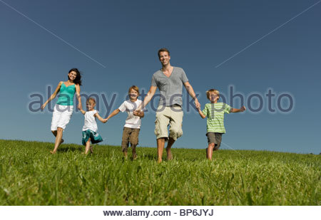 A family of five walking hand in hand through the grass - Stock Photo