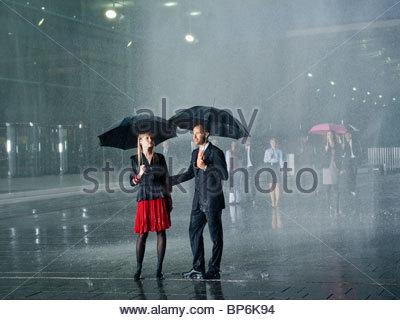 A couple standing in the rain under umbrellas - Stock Photo