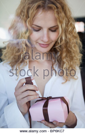 A woman unwrapping a box of chocolates - Stock Photo