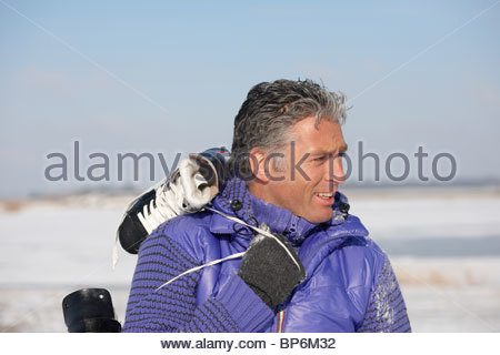 Mature man carrying ice skates over his shoulders - Stockfoto