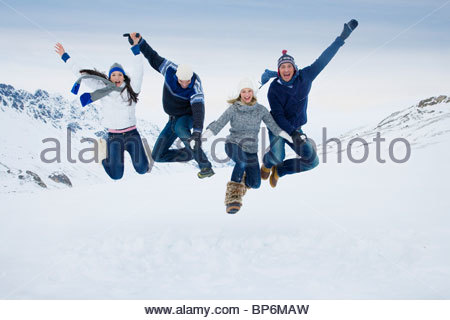 Two young couples jumping in midair in the mountains on winter day - Stockfoto