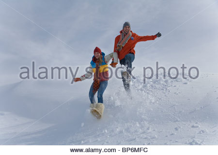 Young couple jumping in snow on winter day - Stockfoto